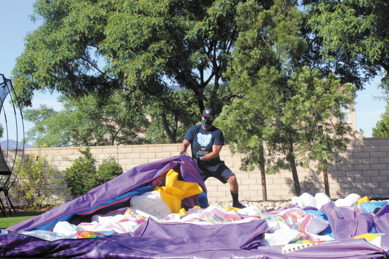 Alberto Frias sets up a bounce house, taking full safety precautions.